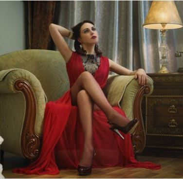 woman red dress seated green chair